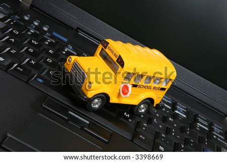 A yellow toy school bus on a laptop computer
