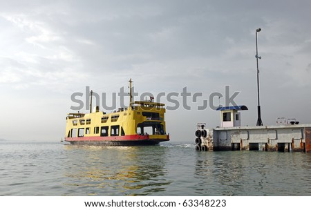 A yellow transport ferry leaving the docks in the early morning to cross the channel carrying vehicles and passengers alike.