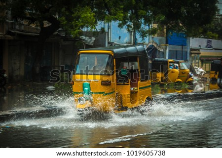 A yellow tuk-tuk or rickshaw in Chennai, India, is driving around on the flooded streets. Water splashing from the wheels on a tuktuk during heavy rain, cyclone or monsoon.