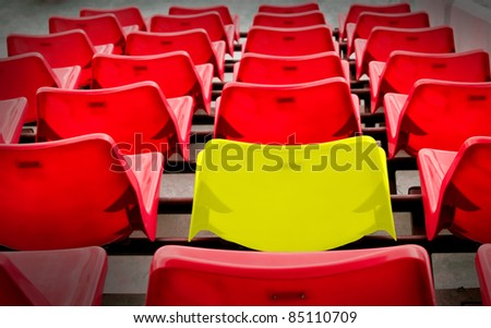 A yellow vip and many red  seat in football stadium
