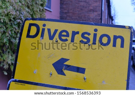 A yellow warning sign for traffic to follow a diversion on the road ahead