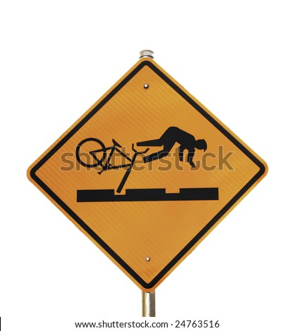 A yellow warning sign shows a bicyclist falling after their bike tire falls into a rut in the road.