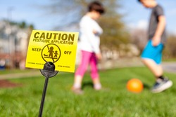 A yellow yard sign warning kids and pets of the recent pesticide spraying and advices them to stay away. Kids are playing soccer in the background regardless. Pesticide use is a big concern.
