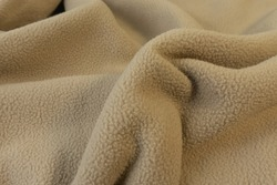 A yellowish brown fluffy short fur fleece fabric look cozy was lying on the floor. Good for background