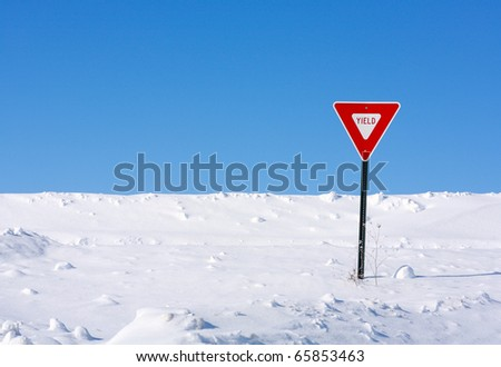 A yield sign sending a message in the middle of a very snowy winter.