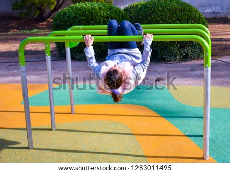 A YONG GIRL MAKING A SOMERSAULT ON THE BAR OF A PLAYGROUND AT THE PARK IN A SUNNY DAY. #1283011495
