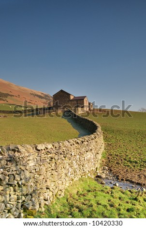 A Yorkshire Dales dry stone  wall leading to a stone barn