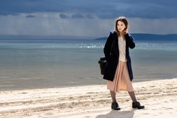 A young adult beautiful girl stands on the shore against the backdrop of an approaching cloud with rain. The woman is wearing a spotty dress, a white sweater and a navy coat.