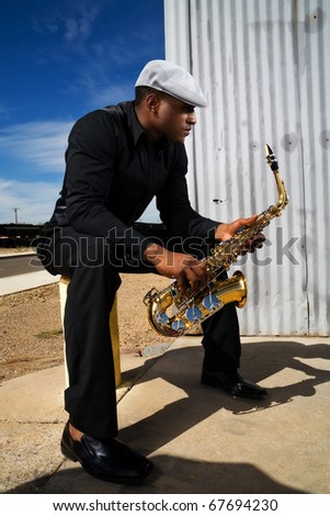 a young adult male saxophone musician - stock photo