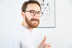 A young adult man smiling and looking at the camera after reading an eye test chart, a vision test board on a white wall. An ophthalmologist, an optometrist eye examination, a test for visual acuity.