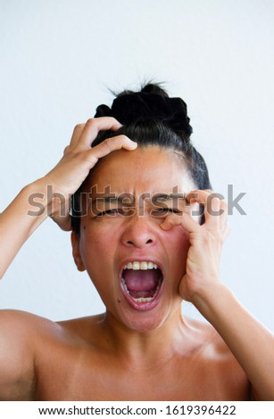 A young adult millennial asian Thai woman screaming and yelling. An emotional stress, mental illness, depression, anxiety and frustration.