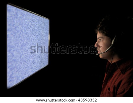 A young adult teenage man is staring into a TV / Computer screen with static all over it at night. He is wearing a headset.