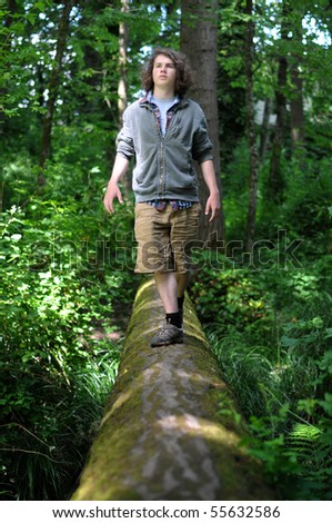 Young adult walking across a fallen tree going across a river in the