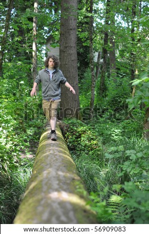 A young adult walking across a fallen tree going across a river in the woods