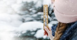 A young adult woman hold in her hand snowy thermometer showing a temperature slightly below freezing. The joy of snow.