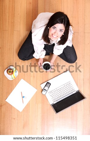 A young adult woman studying on the floor.