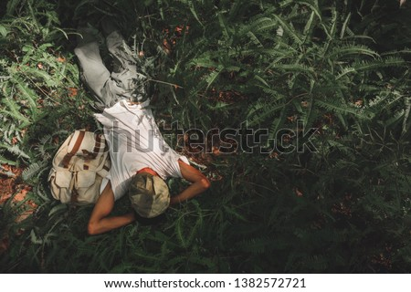 A young adventurer with a backpack resting in a fern forest after tired  .concept of living and adventure on a single holiday in the jungle, forest in Thailand, Phang Nga, Koh Yao Yai.