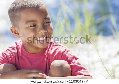 A young African American boy child outside in the summer sunshine