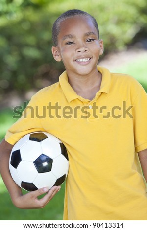 A young African American boy child outside playing holding soccer or football