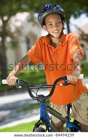 A young African American boy child riding bicycle or bike in the summer
