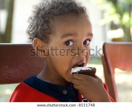 A young african american boy eating birthday cake.
