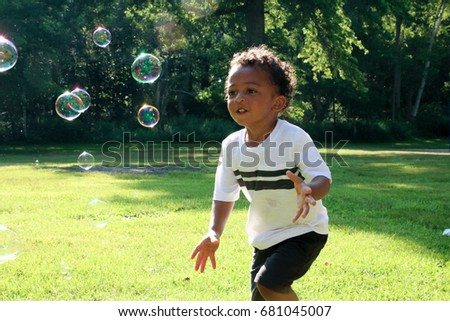 A young African American boy is chasing bubbles in a field.  He is playing in the park, wearing shorts on a hot summer day. Child, diversity, playing, bubbles, running active children
