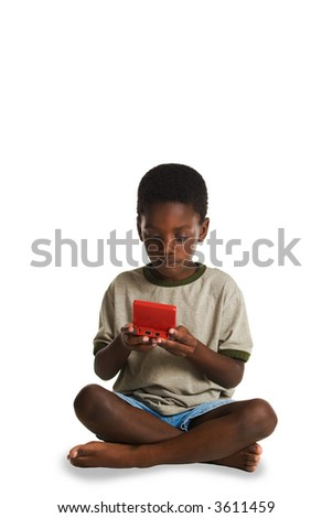 A young, African American boy playing an electronic game. This image is one of a series of conceptual images isolated on white backgrounds.
