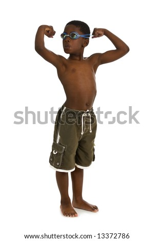 A young African American boy wearing swim trunks and goggles, and showing his muscles. Isolated on a white background.