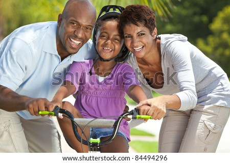 A young African American family with girl child riding her bicycle and her happy excited parents giving encouragement beside her.