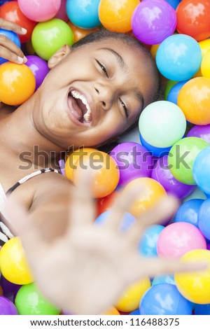 A young African American girl child having fun laughing playing with hundreds of colorful plastic balls