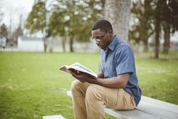 A young African-American male sitting on the bench and reading the Bible