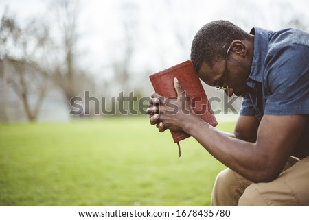 A young African-American male sitting with closed eyes with the Bible in his hands Foto d'archivio ©