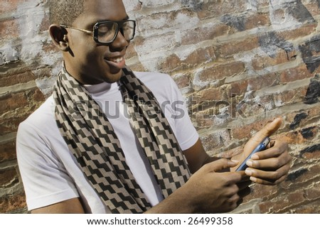 A young African American man on the phone in an urban environment.