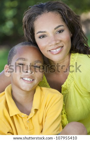A young African American woman & boy child, mother & son, outside in the summer