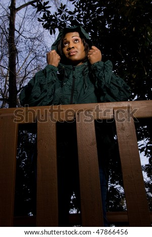 A young African American woman in a raincoat