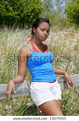 a young African American woman leaning against a wood railing