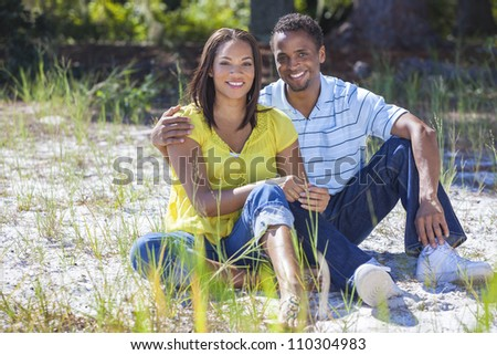 A young African American woman & man couple outside in the summer