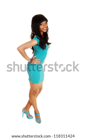 A young African American woman standing for white background with her long curly black hair and a tight turquoise dress and high heels.