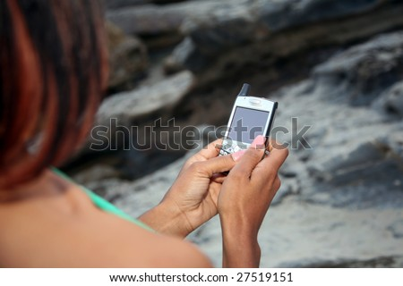 a young african american woman text messages on her cell phone at the beach