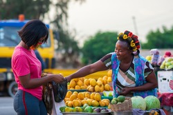 A young African buying fruits from the market and wearing face mask for protection - Receiving a purchased item from a local happy food vendor - Black millennial lifestyle in covid-19 pandemic season.