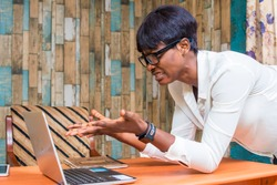 a young african lady feeling frustrated and struggling with using a laptop in an office