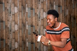 a young african man feeling happy and excited holding his phone and a slip, celebrating