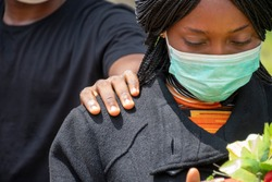 a young african woman mourning, wearing black and holding flowers, someone puts a hand on her to console