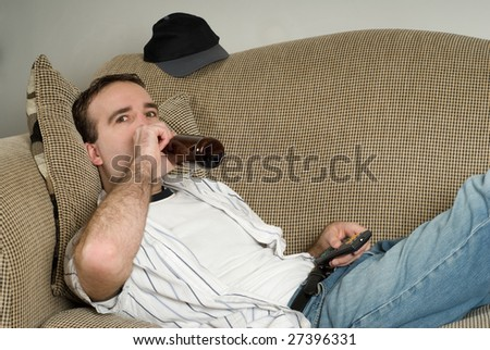 A young alcoholic lying on the couch drinking from a bottle of beer while watching tv