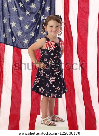 A young American girl in patriotic dress with American flag