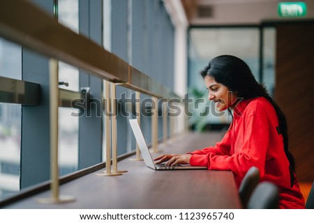 A young and attractive Asian Indian student woman works on her notebook laptop at a wooden desk during the day. She is focused and typing on her notebook; the very image of productivity. #1123965740