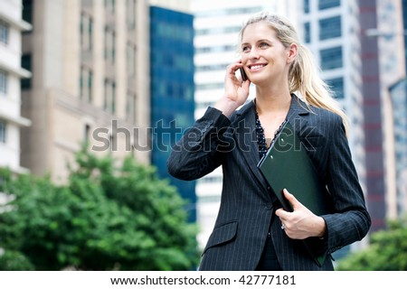 A young and attractive businesswoman using her mobile phone and holding a file under her arm