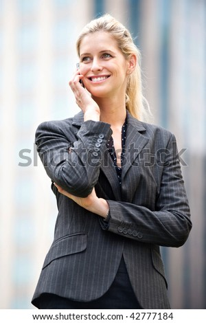 A young and attractive businesswoman using her phone in the city