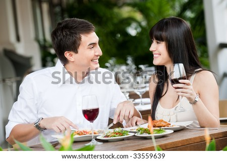 A young and attractive couple dining together in an outdoor restaurant