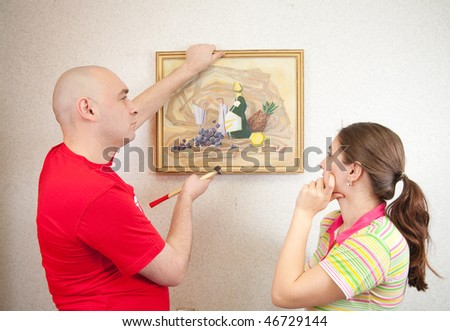 A young and attractive couple hanging up an art picture on their wall